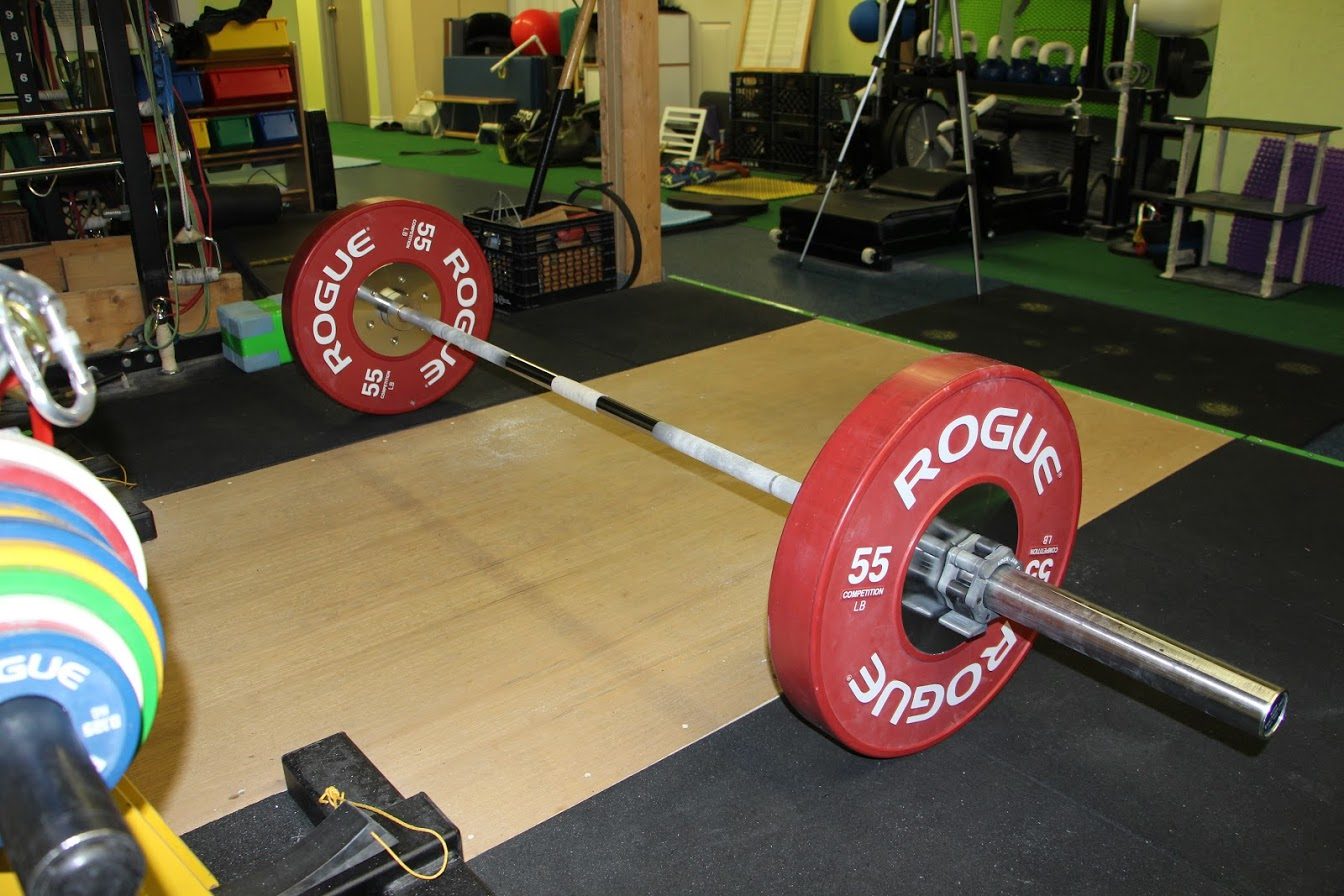 olympic bar loaded with x2 55lb rogue bumper plates on lifting platform